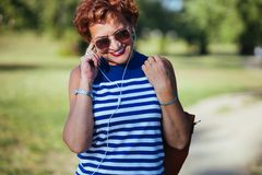 Mature woman listening to the music in the park. Mature woman listening to the music on headphones in the park stock photo