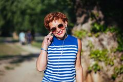 Mature woman listening to the music in the park. Mature woman listening to the music on headphones in the park royalty free stock images