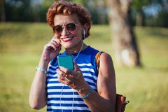 Mature woman listening to the music in the park. Mature woman listening to the music on headphones in the park royalty free stock photography