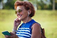 Mature woman listening to the music in the park. Mature woman listening to the music on headphones in the park royalty free stock photos