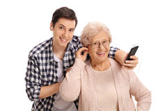 Mature woman listening to music on phone with her grandson Royalty Free Stock Photos