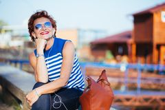 Mature woman listening to the music on smartphone. By the river royalty free stock images