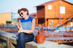 Mature woman listening to the music on smartphone. By the river royalty free stock photo