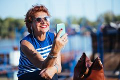 Mature woman listening to the music on smartphone. By the river stock image