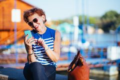 Mature woman listening to the music on smartphone. By the river royalty free stock image