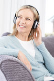 Mature Woman Listening To Music On Wireless Headphones Royalty Free Stock Photos