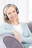 Mature Woman Listening To Music On Wireless Headphones Royalty Free Stock Photo
