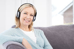 Mature Woman Listening To Music On Wireless Headphones. Mature Woman Listens To Music On Wireless Headphones stock image