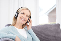 Mature Woman Listening To Music On Wireless Headphones Stock Image