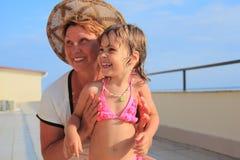 Mature woman with little girl on veranda Royalty Free Stock Photos