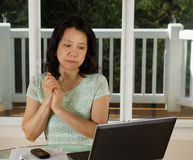 Mature woman looking at computer screen while working from home Royalty Free Stock Photography