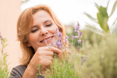 Mature Woman Looking At Flowers Stock Image
