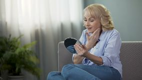 Mature woman looking into a hand mirror, enjoying reflection. Anti-age cosmetics