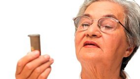 Mature woman looking at her pills Stock Photography