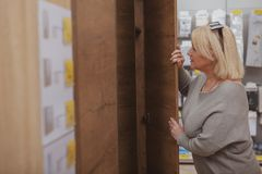 Mature woman shopping at furnishings store. Mature woman looking inside a new wardrobe, shopping for furniture, copy space. Female customer choosing furniture royalty free stock images