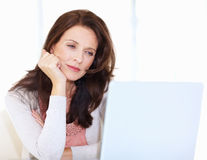 Mature woman looking at laptop  lost in a thought Royalty Free Stock Photo