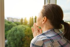 Mature woman looking out the window, close-up view from the back stock photo