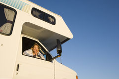Mature woman looking out window of motor home, smiling, portrait, low angle view Royalty Free Stock Photography
