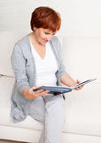 Mature woman looking photo book Royalty Free Stock Images