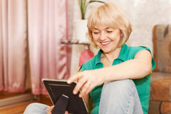 Mature woman looking at photo at home Stock Image
