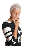 Mature woman looking troubled. Mature woman with short white hair looking troubled and forgetful. isolated on white Stock Photo