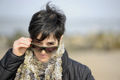 Mature woman lookng over her sunglasses Royalty Free Stock Photo