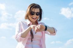 Mature woman looks at the clock stock image
