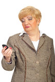 Mature woman looks crooked to cellphone Royalty Free Stock Images