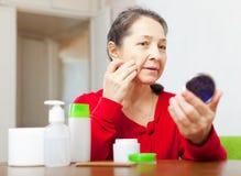 Mature woman looks to facial rhytid Royalty Free Stock Photos