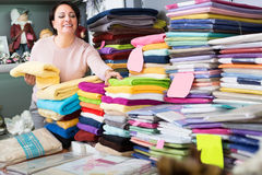 Mature woman with loop towels. Happy mature woman with loop towels and bed sheets in textile store Royalty Free Stock Photography