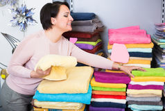 Mature woman with loop towels. Portrait of mature woman with loop towels and bed sheets in textile store stock photo