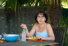 Mature woman lunch in the garden Royalty Free Stock Image