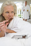 Mature woman lying on bed, holding piece of chocolate, mature man standing in background Royalty Free Stock Photos