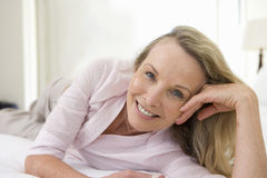 Mature woman lying on bed, smiling, portrait, close-up Stock Photo