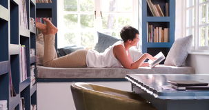 Mature Woman Lying On Couch At Home Reading Book. Mature woman lying on couch at home reading a book.Shot in 4k on Sony FS700 at frame rate of 25fps stock footage