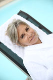 Mature woman lying on a long chair Stock Images
