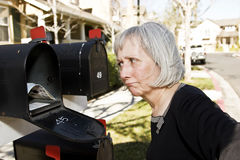 Mature Woman at Mailbox. An attractive mature woman is perplexed at what is in her mailbox Stock Photo