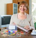 Mature woman makes bracelets at home Royalty Free Stock Images