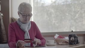 Mature woman makes an online purchase using a tablet in the cafe. Youthful pensioner pays the purchase online by credit card. Modern pensioner use plastic stock video footage