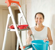 Mature woman makes repairs at home Stock Photo