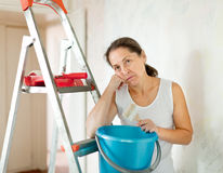Mature woman makes repairs at home. Weariness mature woman makes repairs at home Stock Image