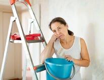 Mature woman makes repairs at home Stock Image