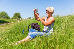 Mature woman makes selfie photos with a phone Royalty Free Stock Photography