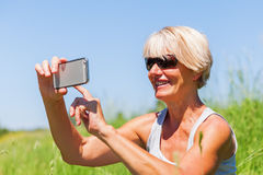 Mature woman makes selfie photos with a phone Stock Photography