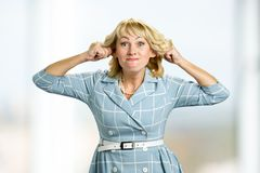 Mature woman making funny face. Adult woman making grimace stretching ears Stock Images
