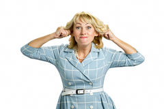 Mature woman making funny face. Middle aged woman in dress making grimace stretching ears isolated on white background Stock Photography