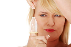 Mature woman making hole in condom Stock Photo