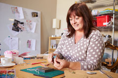 Mature Woman Making Jewelry At Home royalty free stock photography