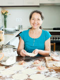Mature woman making meat dumplings Stock Photos