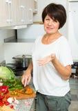 Mature woman making salad Stock Photos